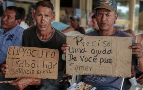 Venezuelan workers in Roraima hold signs asking for jobs.