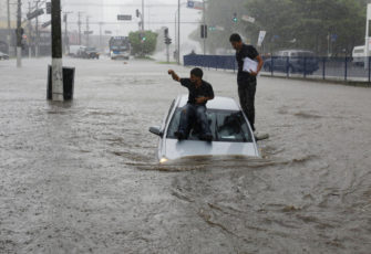 Driver gets stuck with his car on a flooded avenue during heavy rains. climate change
