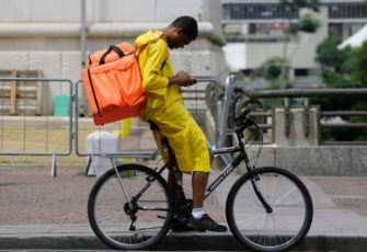 A delivery app bike boy wearing a raincoat check his mobile phone in downtown SP business district